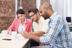 Focused business people taking down important notes Stock Photos