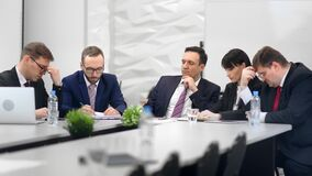 Focused business people thinking brainstorming in formal meeting at white room interior