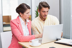 Focused business people working together on laptop. In the office Royalty Free Stock Images