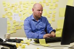 Focused Businessman. A hard working office worker with a lot do. Messy office royalty free stock photo