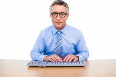 Focused businessman with glasses typing on keyboard Royalty Free Stock Image