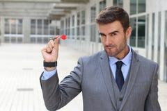 Focused businessman holding a dart Stock Photos