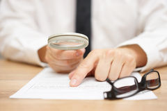 Focused Businessman Is Reading Through Magnifying Glass Stock Image