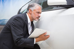 Focused businessman looking at the car body Royalty Free Stock Photography