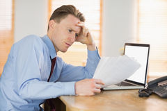 Focused businessman reading document at desk Stock Photo