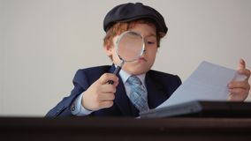 Focused businessman researching paper document with magnifying glass in office. Concentrated business boss using. Magnifier for scrutinize. Detective stock video footage