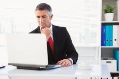 Focused businessman in suit using his laptop Stock Photos