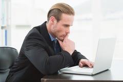 Focused businessman in suit using laptop Stock Images