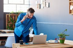 Focused businessman talking on his cellphone and using a laptop. Focused mature businessman talking on a cellphone and leaning over a laptop at his desk while Royalty Free Stock Photography