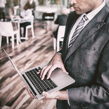 Focused businessman using laptop. While standing in office Royalty Free Stock Images
