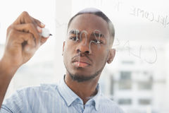 Focused businessman writing on clear board Stock Photos