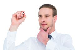 Focused businessman writing with hand on chin Royalty Free Stock Images