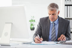 Focused businessman writing something down Stock Images