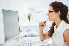 Focused businesswoman with glasses using computer Royalty Free Stock Image