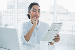 Focused businesswoman reading newspaper sitting at her desk Royalty Free Stock Photography