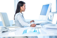 Focused businesswoman taking notes while working on computer. In office Stock Photography