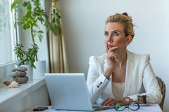 Focused businesswoman thoughtfully with laptop in office. Royalty Free Stock Image