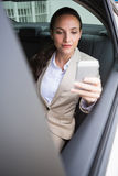Focused businesswoman using her phone Stock Images