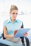 Focused businesswoman wearing glasses using tablet Stock Image