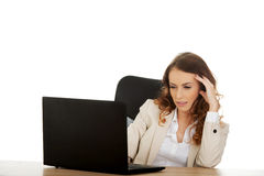 Focused businesswoman working on laptop. Royalty Free Stock Image