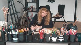 Artist works at the desk. Focused busy artist drawing a picture in the sketchbook, sitting at the desk packed with number of coloured pencils, wearing black stock footage