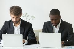 Focused busy diverse businessmen working on laptops sharing offi. Focused busy diverse businessmen working independently on laptops online share office desk stock photography
