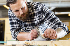 Focused carpenter work with plane on wood plank in workshop. Hard working craftsman working with planer in a workshop for woodwork. Handsome man with tattoo and Royalty Free Stock Photography