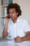 Focused casual businessman on the phone taking notes at desk Royalty Free Stock Photo