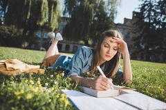 Young woman studying in park. Focused caucasian student doing homework while lying on grass in park Royalty Free Stock Images