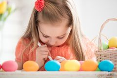 Focused child creating drawings on colorful dyed eggs. Easter traditions and preparations Stock Photo