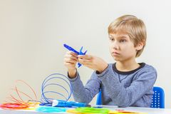 Focused child with 3d printing pen creating a plane.  stock image