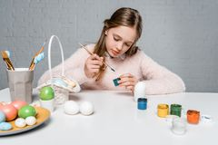 Focused child painting easter eggs at table. Adorable focused child painting easter eggs at table Stock Photos