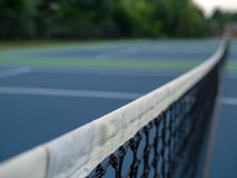Focused close up of a tennis court net with background in blur royalty free stock image
