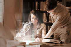 Focused college students analysing dna on digital interface. In university library royalty free stock photo