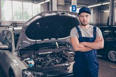 Focused concentrated caucasian expert mature virile harsh mechan. Ic with bristle at work shop, arms crossed, in special safety outfit uniform, t shirt, hat head Stock Image