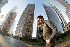 A focused and concentrated handsome man talking on his mobile ph. One walking among skyscrapers the city financial center Royalty Free Stock Photography