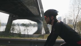 Focused confident cyclist on a bicycle. Sun shines through. River and bridge in background. Close up side view. Cycling concept. stock video footage