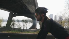 Focused confident cyclist on a bicycle. Sun shines through. River and bridge in background. Close up side view. Cycling concept. S stock video footage