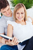 Focused couple reading a book together on the sofa royalty free stock images