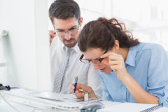 Focused coworkers looking photos together Stock Photos