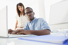 Focused coworkers using laptop and looking at camera Royalty Free Stock Photo