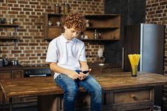 Focused curly haired child enjoying music in kitchen. Calmness and serenity. Preteen chestnut haired boy sitting on a wooden kitchen island and concentrating on Royalty Free Stock Image