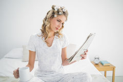 Focused cute blonde wearing hair curlers reading newspaper Stock Image