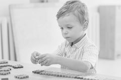 Focused cute little child collects puzzles. With numbers at the table  black and white Stock Photo