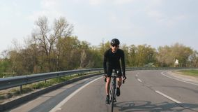 Focused Cyclist on a road bicycle riding towards camera at sunset. Biker wearing black jersey and shorts. Cycling concept. Focused Cyclist on a road bicycle stock video