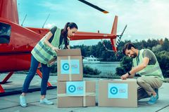Focused dark-haired volunteers opening boxes with humanitarian help stock photography