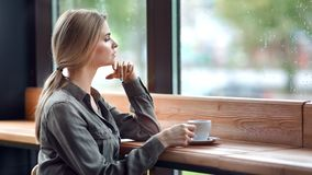 Focused depressed young woman looking out of wet window rainy weather sitting at cafe. Having coffee medium shot. Sad attractive female dreaming enjoying stock video footage