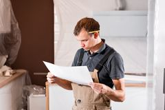 Focused diligent worker inspecting room and planning repairs work. repair of the dining room in the house, kitchen royalty free stock photo