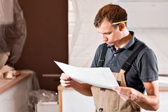 Focused diligent worker inspecting room and planning repairs work. repair of the dining room in the house, kitchen stock photo