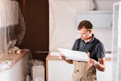 Focused diligent worker inspecting room and planning repairs work. repair of the dining room in the house, kitchen stock image
